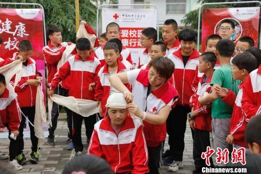 """6月11日至13日,中国红十字基金会在甘肃省援建的首批11个""""博爱校医室""""落成。图为在中国红基会、庆阳市西峰区红十字会救护师资指导下,显胜实验学校学生进行创伤包扎的实操技能演练。 付春来 摄"""