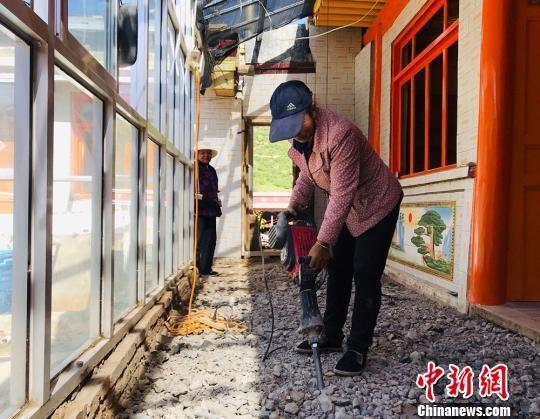 博峪村村民李旦知草手持�C器�整地面。 艾�c�� �z