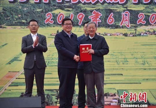 """和政县官方向油菜遗传育种学家、中国工程院院士傅廷栋(右)颁发""""特别顾问""""聘书。(资料图) 钟欣 摄"""