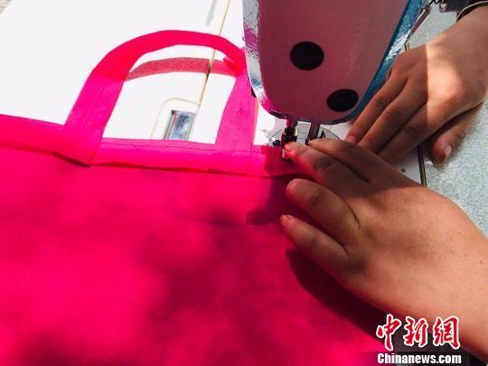 与普通扶贫车间相比,残疾人扶贫车间工作仅将布料缝制成为手提袋。 艾庆龙 摄