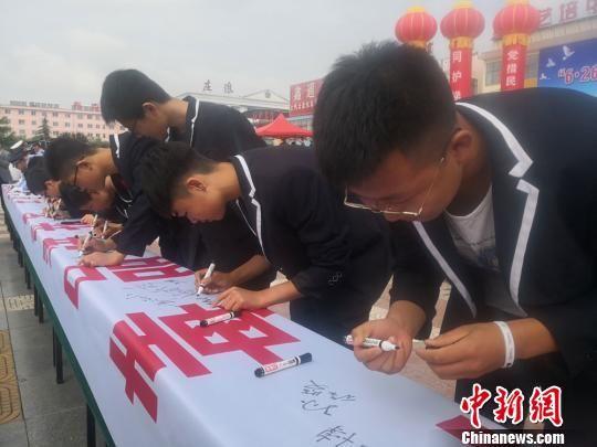 图为民众在拒毒横幅上签名。 崔琳 摄