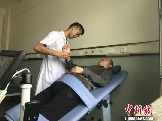图为康复治疗师借助机器为患者治疗。 闫姣 摄