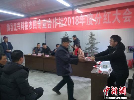 图为去年为甘肃徽县当地民众分红。(资料图) 钟欣 摄