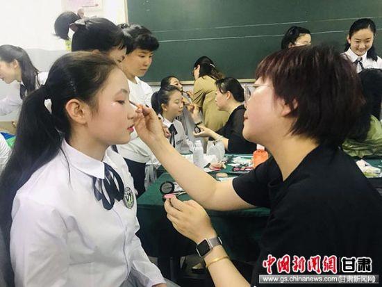 图为家长为学生化妆。艾庆龙 摄