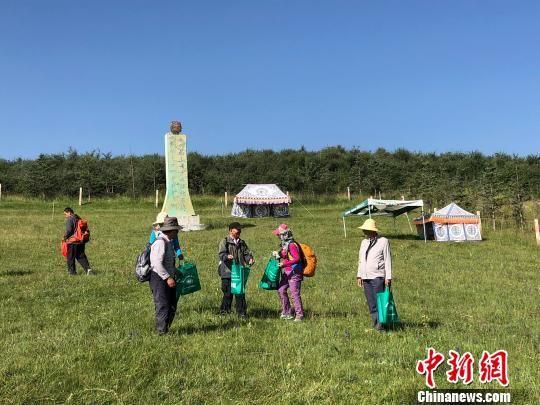 图为甘肃民众自发在草原上捡垃圾倡环保。(资料图) 徐雪 摄