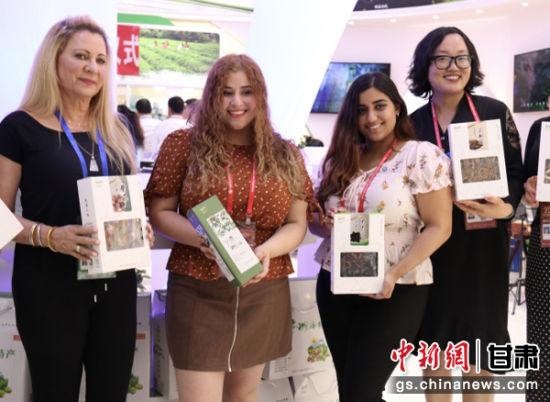 图为在兰洽会陇南市展馆中,外国客商手捧选购的当地农特产合影。