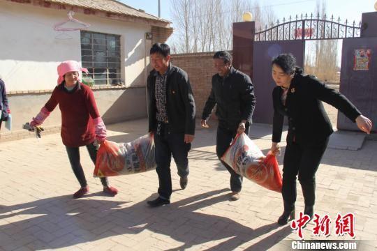 图为高台县妇联主席王姗(右一)给贫困户送化肥。(资料图) 钟欣 摄