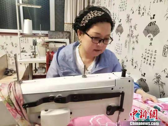 图为丁桂英正在进行机绣。 钟欣 摄