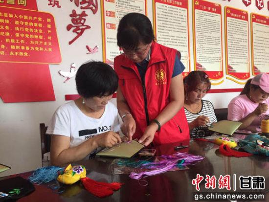 """甘肃镇原县文化志愿者任艳艳带动""""贫困妈妈""""手工制作,让她们的口袋鼓起来。侯志雄 摄"""