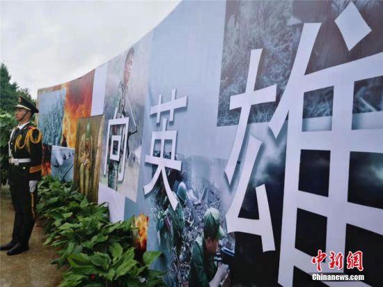 图为一场大雨中,甘肃省兰州市举行参战牺牲烈士骨灰安葬仪式,将9具参战牺牲烈士骨灰迁移安葬于兰州市烈士陵园。 史静静 摄