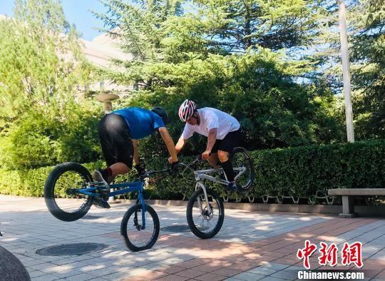 王龙(左)和辛彦君在进行前轮单立技巧时长比赛。 艾庆龙 摄