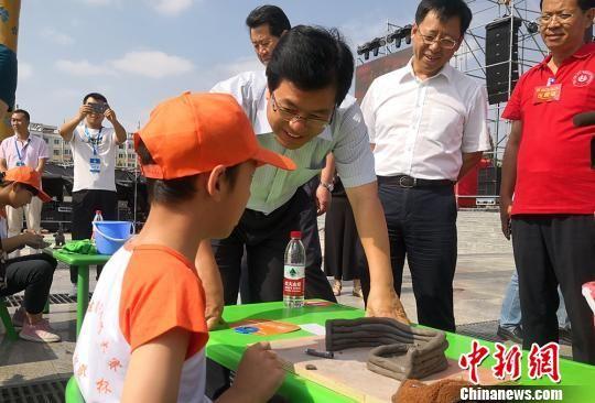 图为专家指导小学生陶艺制作。 刘玉桃 摄