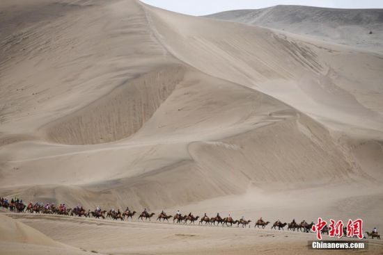 游客骑骆驼在敦煌鸣沙山月牙泉景区游览,驼队宛如长龙。