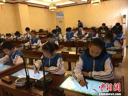 图为小学生正在使用智能书法系统练习写书法。(资料图) 林鹏 摄
