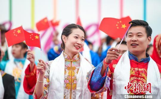 图为新人们手拿五星红旗祝福祖国。 杨艺锴 摄