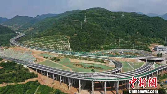 """""""逢山开路、遇水架桥""""……新中国成立70年以来,甘肃公路总里程由实际能通行汽车的3200多公里,发展为目前逾14.32万公里,全省公路通车总里程增加44倍。图为陇南山区蜿蜒的高速公路。 张宾 摄"""