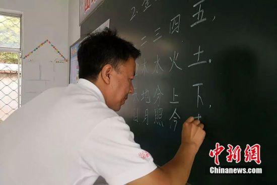杨锋正在写黑板书。