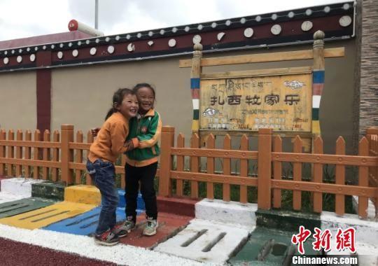 图为碌曲县尕秀村藏族小孩在牧家乐门前嬉戏玩耍。 闫姣 摄