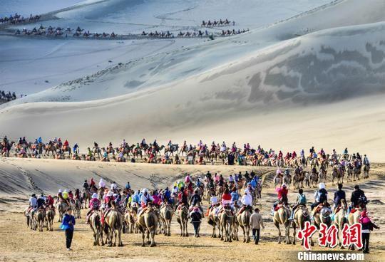 2019年7月18日,中外游客在敦煌鸣沙山月牙泉景区骑骆驼观光游览,形成近2公里长的宛如长龙的观光驼队。(资料图) 王斌银 摄