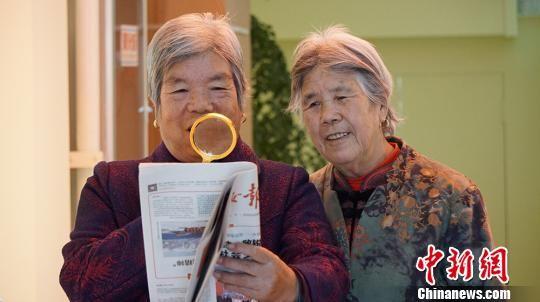 """图为社区居民从""""便民服务柜""""借放大镜看报纸。 魏建军 摄"""