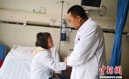 图为甘肃省中医药大学附属医院院长张晓刚查看格日草康复情况。 南如卓玛 摄