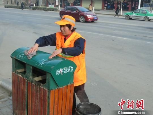 图为赵灵英擦垃圾桶。(资料图) 钱彦虎 摄