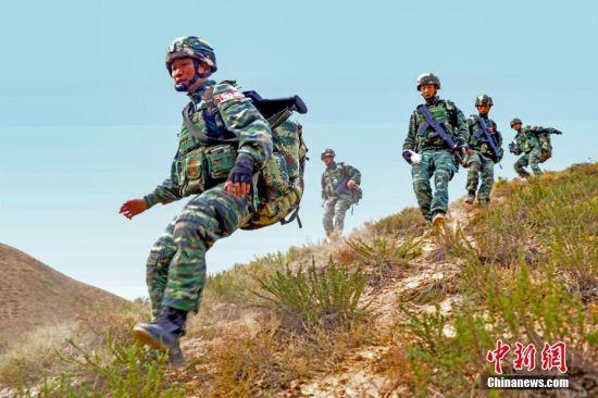 """""""魔鬼周""""极限训练为期7天6夜,每天训练时间长达18个小时,人均负重30公斤,围绕极限体能、实战技能、综合战术、心理挑战等内容,采取计划与随机导调结合,完成融体能、技能、战术、智能、心理、野外生存于一体5大类共35个科目的训练,全面提升特战官兵综合反恐作战能力,锤炼特战队员顽强战斗精神、密切团队意识和过硬的综合作战能力,为遂行多样化任务打下坚实基础。负重前进。 侯崇慧 摄"""