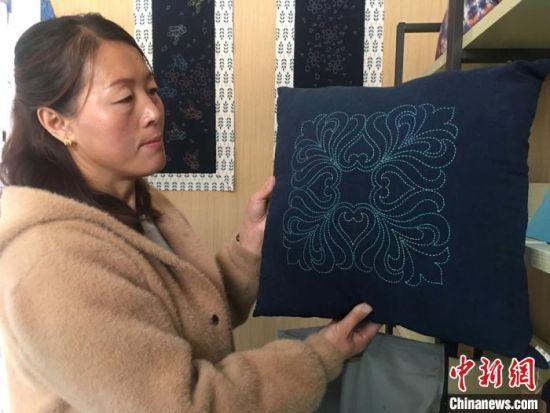 云田�三十里�村民王彩琴手提已完成的刺�C茶��|到作坊�I取手工�M,她向�者展示�C娘��制作的刺�C抱枕。 ��婧 �z