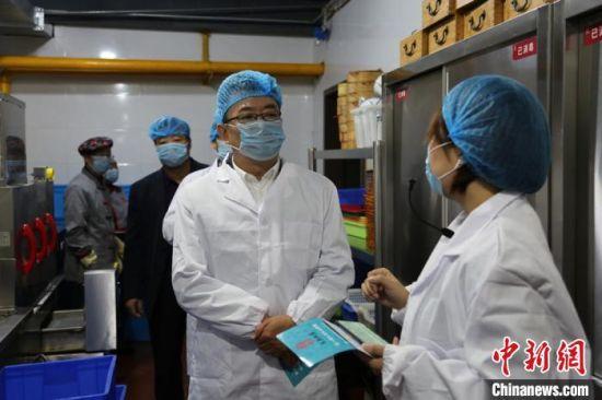 """图为甘肃省市场监管局、省教育厅相关负责人了解""""明厨亮灶""""经验做法。 史静静 摄"""
