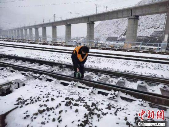 图为中铁兰州局集团有限公司职工干部扫雪保障旅客安全出行。 关杰 摄