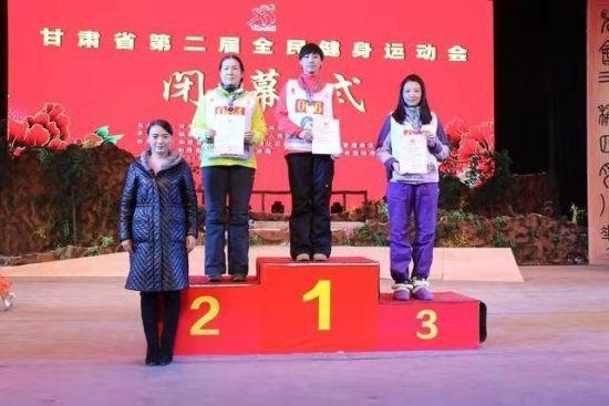 """甘肃省体育局办公室主任王斌,宣读甘肃省第二届全民健身运动会""""体育道德风尚奖""""名单,并为滑雪比赛获奖运动员颁奖。"""