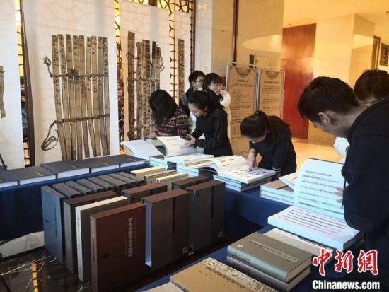 图为民众现场翻阅近日出版发行的《悬泉汉简》《玉门关汉简》。 冯志军 摄