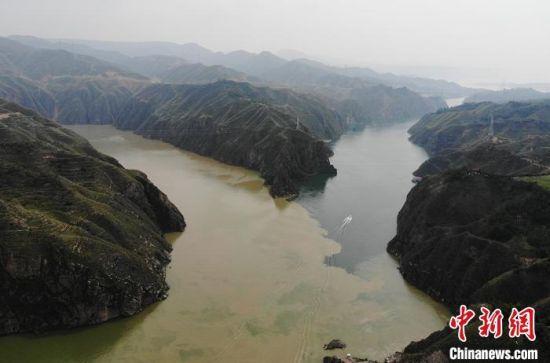 """图为甘肃永靖县刘家峡远眺洮河汇入黄河,入河口呈现出""""二龙戏珠""""的交汇奇观。两条河流汇聚于此,""""泾渭分明"""",交融却不渗透,再加上河中石山,犹如两条巨龙游戏于此,在当地这景象也被称为""""二龙戏珠""""。(资料图) 杨艳敏 摄"""