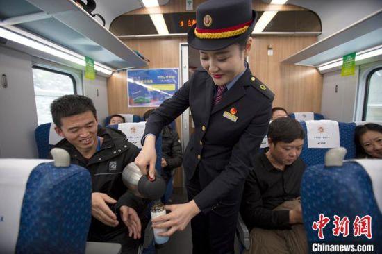 图为客运乘务员为旅客递上热水。 兰州局集团宣传部供图