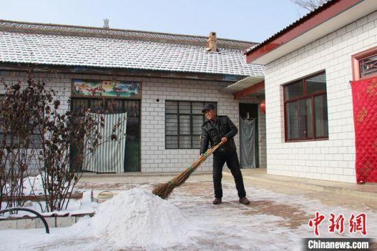 1月21日,贾海峰清扫院子里的积雪。 盘小美 摄