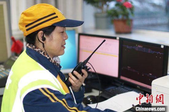 李春玲正在车站密切关注区间来车信息,并通过对讲机向现场通知。 王光辉 摄