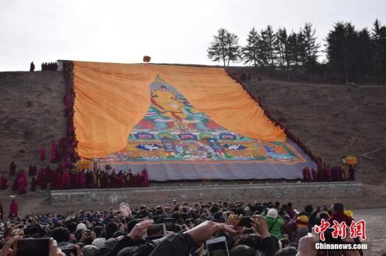 """资料图:2016年2月20日,农历正月十三,有着""""世界藏学府""""之称的甘肃拉卜楞寺举行了一年一度的正月晒佛节。何龙 摄"""