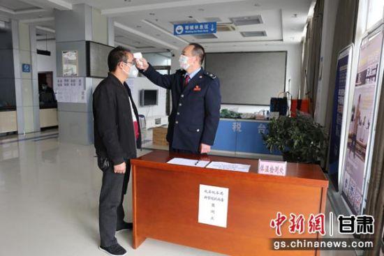 图为成县税务局为预约办税的纳税人测量体温。