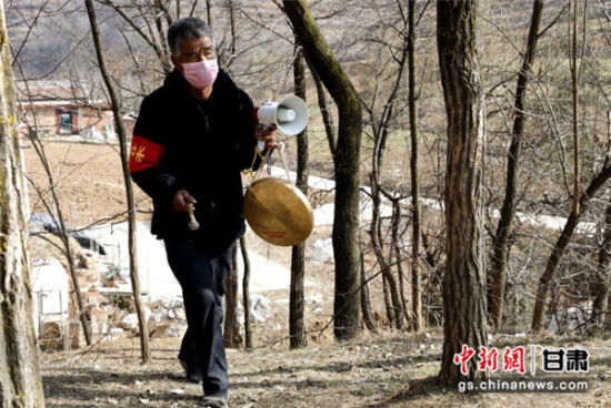 """图为甘肃陇南西和县刘集村""""银发志愿者""""徒步在较偏僻的居住点敲锣宣传防疫知识。吕宏 摄"""