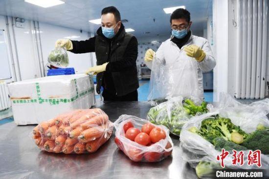 """图为兰州""""共享员工""""为线上下单的客户分拣包装蔬菜。 杨艳敏 摄"""