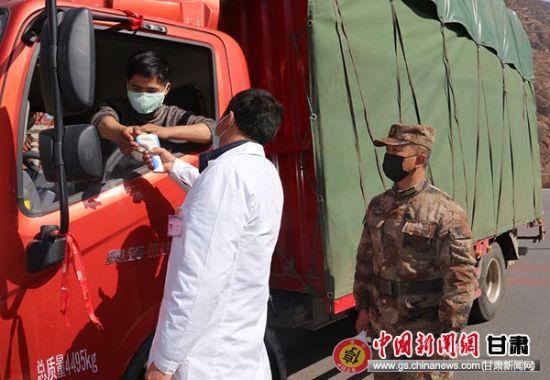 图为宕昌县新城子藏族乡民兵沙艳军正在协同村医检测过往人员体温。