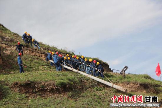 2019年,甘肃临洮县供电公司配农网施工人员正在全力以赴移栽电线杆。