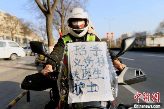 """兰州""""护医使者""""张卫星摩托车前贴着""""招手义务接送医生护士""""的牌子。 高展 摄"""