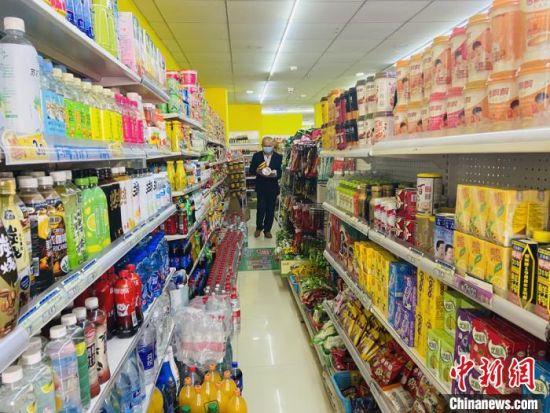 图为郭平安去超市购买食物。 高康迪 摄
