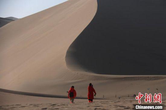 图为游客在甘肃省敦煌市鸣沙山月牙泉景区游览。 张晓亮 摄