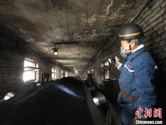 图为李红彪手举矿灯检查生产线运作。 张婧 摄