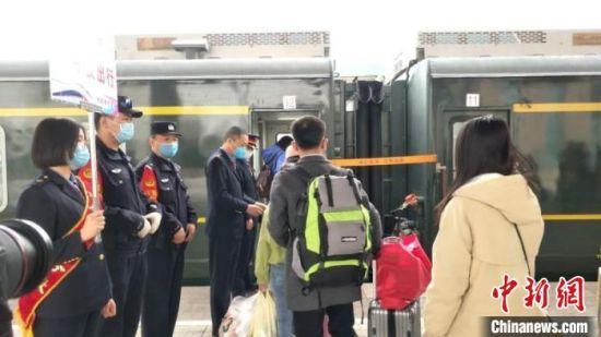 图为中国铁路兰州局集团公司工作人员在站台对进疆务工旅客进行引导,确保复工人员有序出行。 张涛 摄