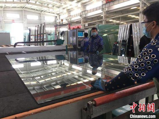 图为白银市白银区一家钢化玻璃厂车间内切割生产线工作。 张婧 摄