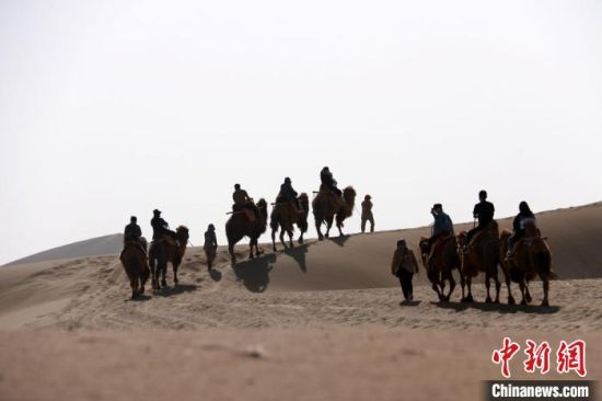 图为游人骑骆驼游览鸣沙山。 张晓亮 摄
