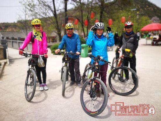 图为骑行爱好者在泾明乡白家村游玩。